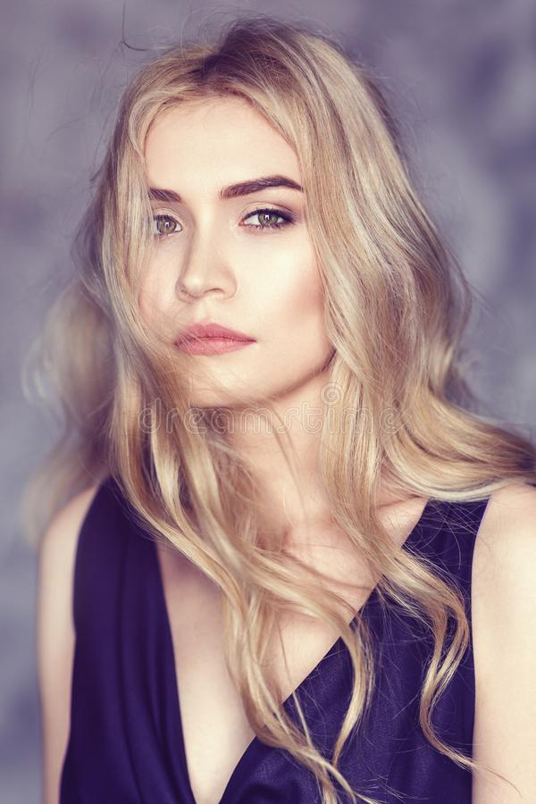 Portrait of a young beautiful girl with blond hair and a thoughtful look, close-up royalty free stock photography