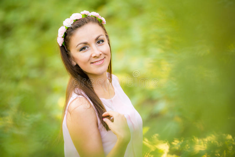 Portrait of a young beautiful girl on blurred background of green foliage royalty free stock photography