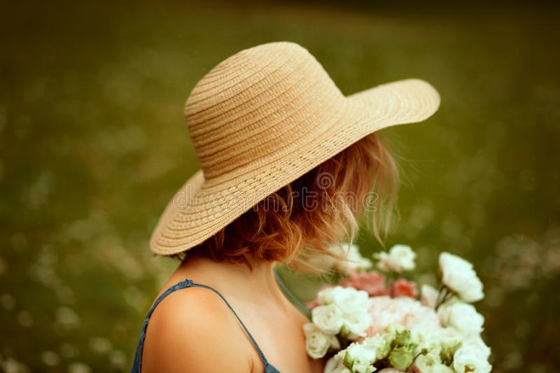 Portrait of young beautiful girl with curly hair from the back in the summer hat keepings flowers. Summertime. stock photography