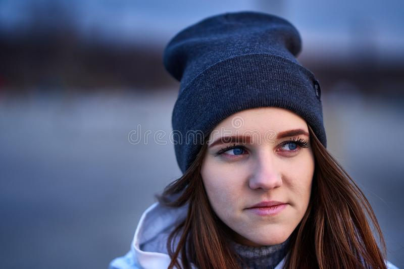 Portrait of a young beautiful girl with dark brown hair in a sports hat. In the first rays of the morning rising sun in an autumn cold morning stock images