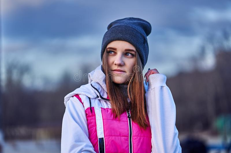 Portrait of a young beautiful girl with dark brown hair in a sports hat and jacket. In the first rays of the morning rising sun in an autumn cold morning stock photography