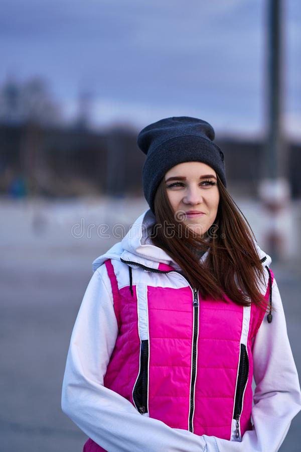 Portrait of a young beautiful girl with dark brown hair in a sports hat and jacket in the first rays of the morning rising sun. In an autumn cold morning stock images
