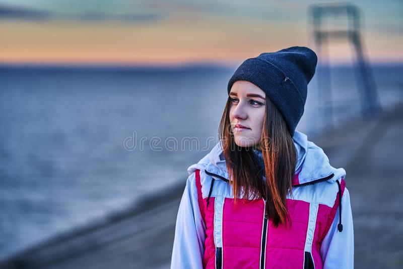 Portrait of a young beautiful girl with dark brown hair in a sports hat and jacket in the first rays of the morning. Rising sun in an autumn cold morning stock image