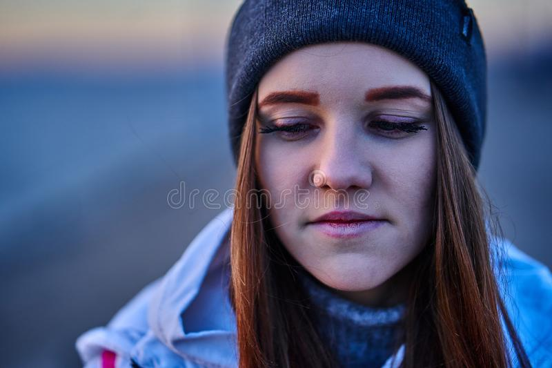 Portrait of a young beautiful girl with dark brown hair. In a sports hat and jacket in the first rays of the morning rising sun in an autumn cold morning stock image
