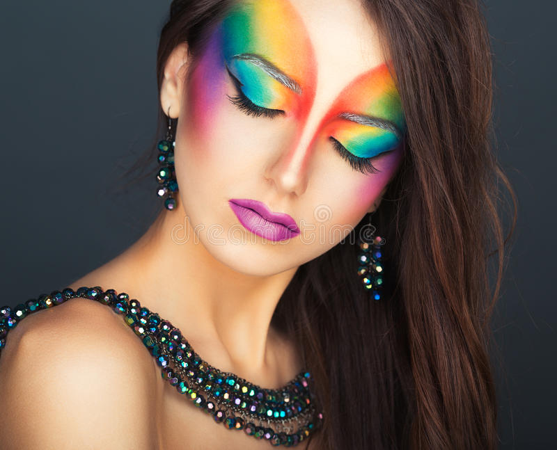 Portrait of a young beautiful girl with a fashion bright multicolored makeup royalty free stock photography