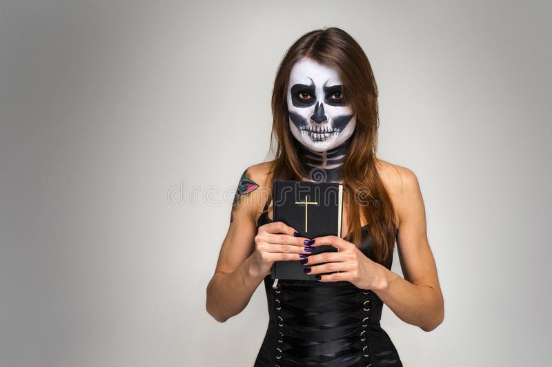 Portrait of young beautiful girl with fearful halloween skeleton makeup holding Holy Bible over gray background royalty free stock image