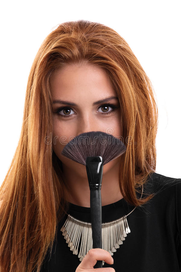 Portrait of a young beautiful girl holding a make up brush stock photos