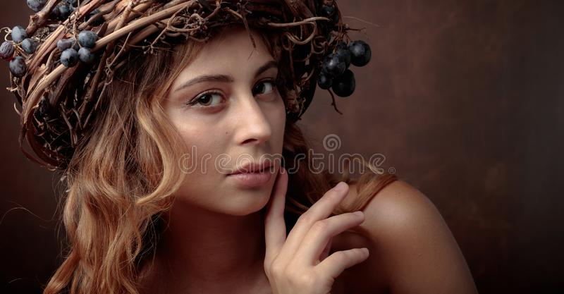 Portrait of young beautiful girl with long wavy hair. Vine wreath with blue grapes on a head. Model look at camera. Copy space royalty free stock photo
