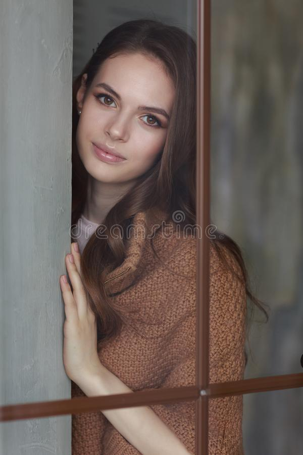 Portrait of a young beautiful girl looking through a window royalty free stock photos