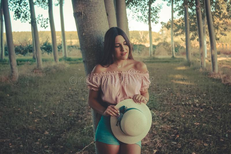 Portrait of a young beautiful girl outddor in white sun hat in contemplative way. Outdoor portrait of a young beautiful brunette girl holding in hands a white stock image