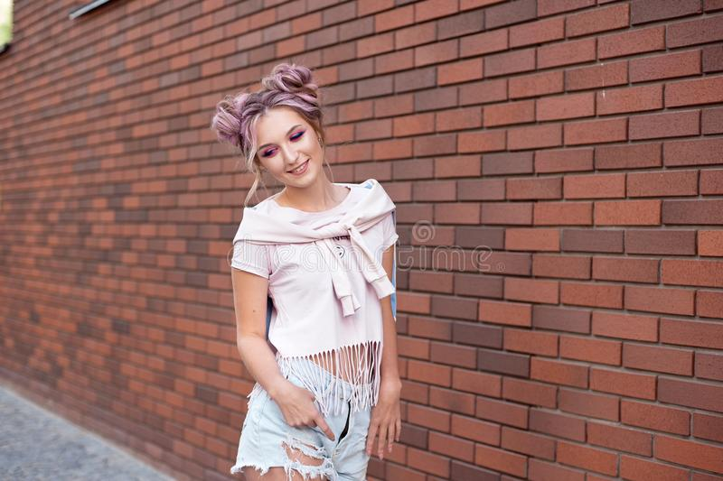 Portrait of a young beautiful girl with pink hair bun smiling against a red brick wall. stock photos