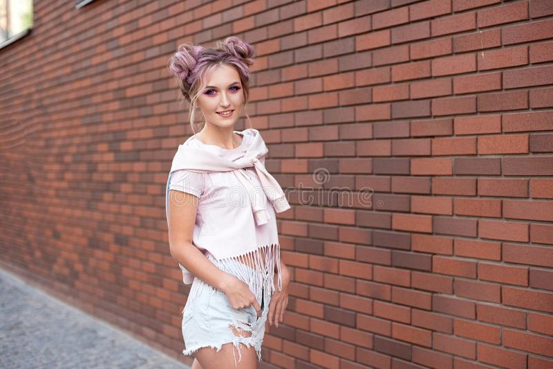 Portrait of a young beautiful girl with pink hair bun smiling against a red brick wall. stock photo