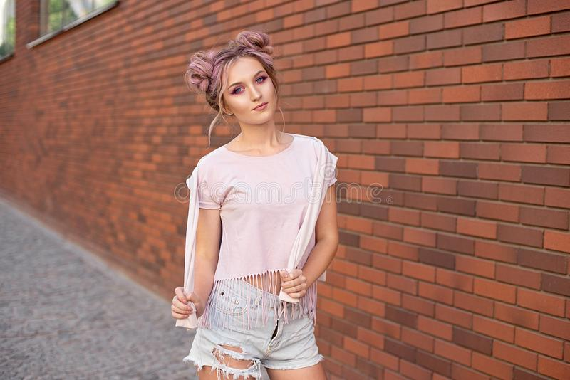 Portrait of a young beautiful girl with pink hair bun smiling against a red brick wall stock photography