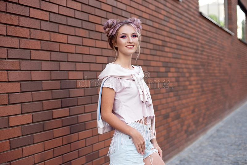 Portrait of a young beautiful girl with pink hair bun smiling against a red brick wall. royalty free stock photo