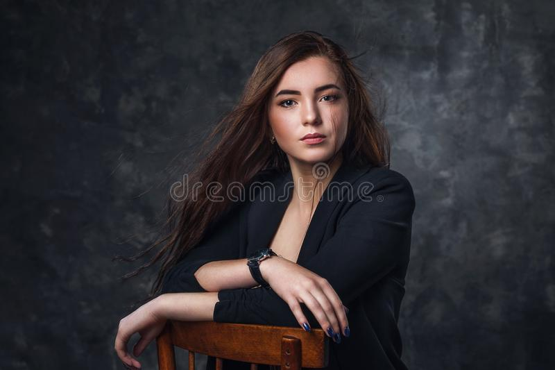 Portrait of a young beautiful girl posing in a black suit on a wooden chair stock photos