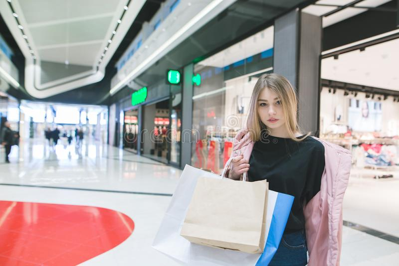 young beautiful girl with shopping bags in her hands against shopping malls. Shopping concept stock photography