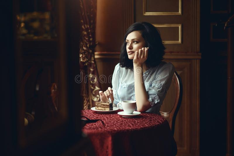 Portrait of young beautiful girl sitting at the table in the cozy coffee shop and looking at the window thoughtfully, her face bur royalty free stock images