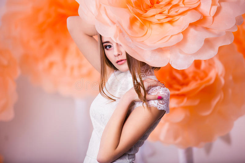 Portrait of young beautiful girl in spring paper flowers. Young beautiful girl posing in paper flowers in spring studio royalty free stock images