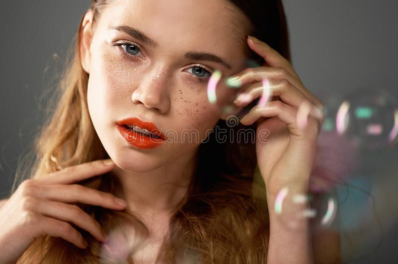 Portrait of young beautiful girl in Studio, with professional makeup.Beauty shooting.The beauty of soap bubbles. The royalty free stock photo