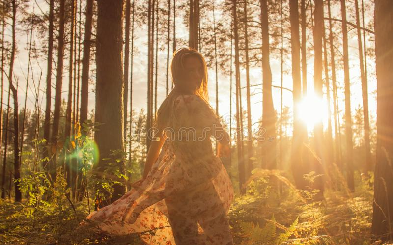 Portrait of young beautiful girl in summer dress in forest that dancing. On the sunset stock photos