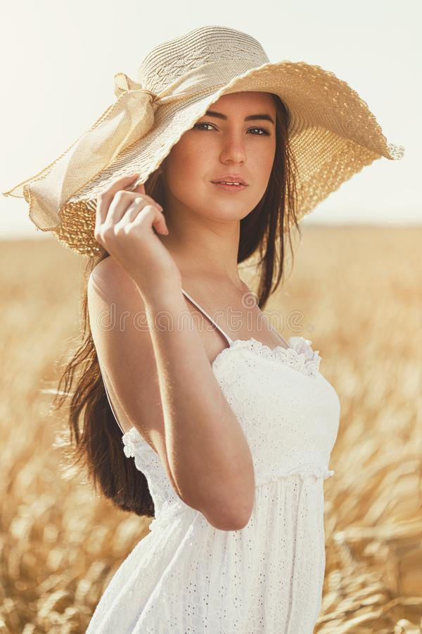 Portrait of a young beautiful girl in a white dress in the sun royalty free stock photos