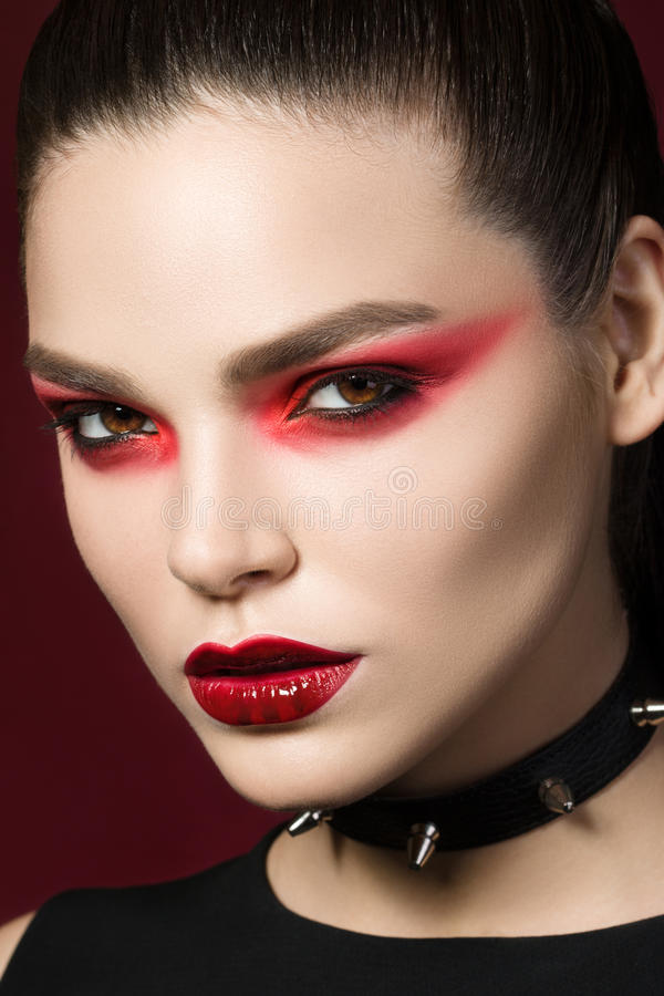 Portrait of young beautiful gothic woman. Young beautiful gothic woman with white skin and red lips with bloody drops wearing black collar with spikes. Red stock photo