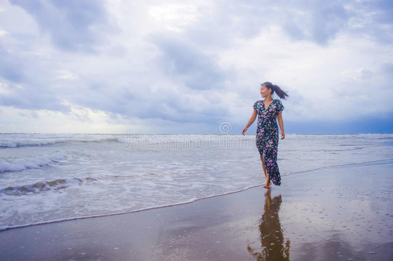 Portrait of young beautiful and happy Asian Chinese woman on her. 20s or 30s wearing long chic dress walking alone on beach sea water enjoying holidays and the stock photos