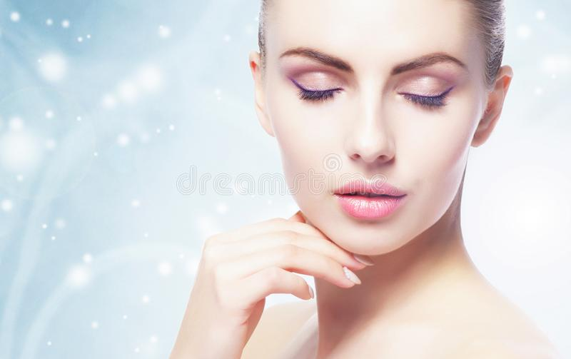Portrait of young, beautiful and healthy woman: over winter background. Healthcare, spa, makeup and face lifting concept. Portrait of young, beautiful and royalty free stock photography