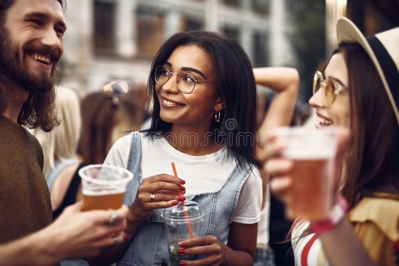 Cheerful hipster friends enjoying drinks while spending time outdoors stock images