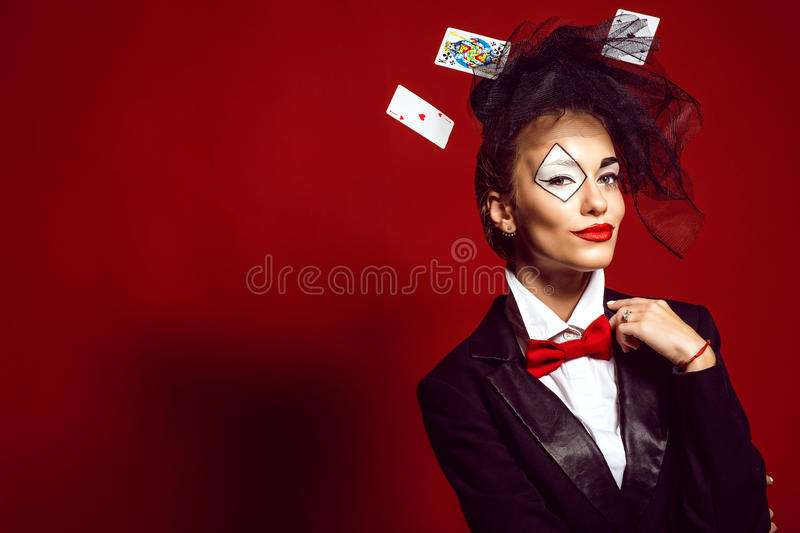Portrait of a young beautiful lady croupier with playing cards. stock photos