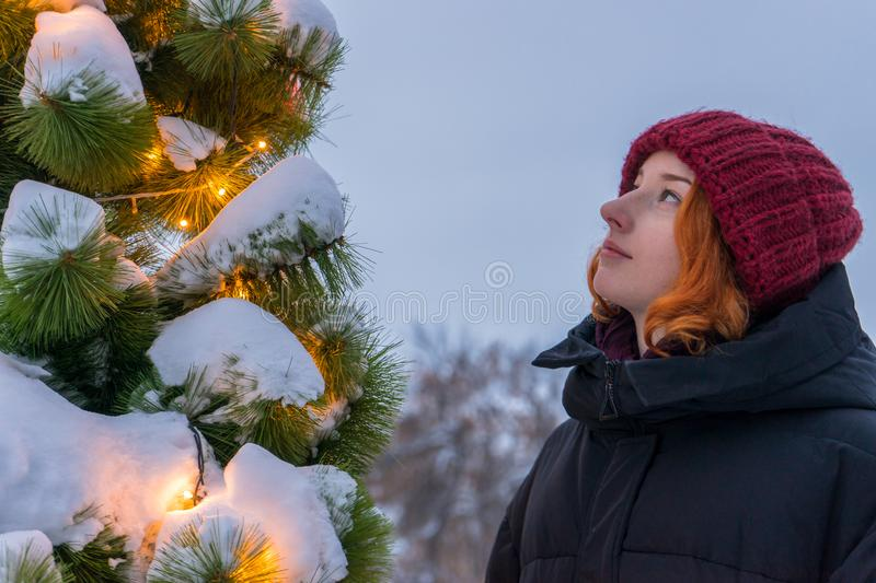 Portrait of young beautiful lady near decorated Christmas tree at city street in winter. Teen girl looking at new year spruce in stock photo