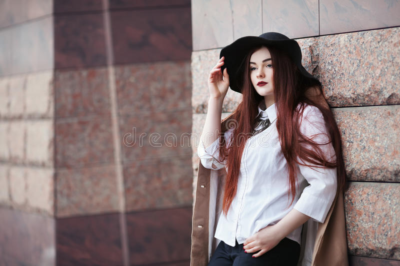 Portrait of young beautiful lady wearing stylish classic clothes posing at street. Girl looking forward. Plus size model royalty free stock photo