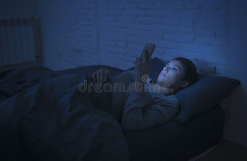 Portrait of young beautiful latin woman using mobile phone late night sleepless lying in bed in the dark in smartphone and interne stock photos