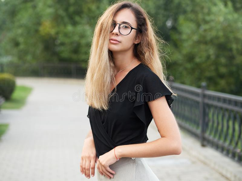 Portrait of young beautiful long hair woman wearing black blouse, holding mobile phone at summer green park path background. royalty free stock photography