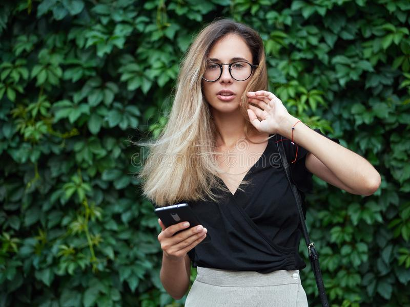 Portrait of young beautiful long hair woman wearing black blouse, holding mobile phone at summer green park against ivy background stock photography