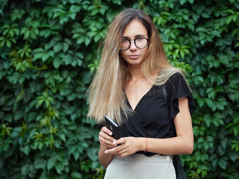 Portrait of young beautiful long hair woman wearing black blouse, holding mobile phone at summer green park against ivy background royalty free stock image