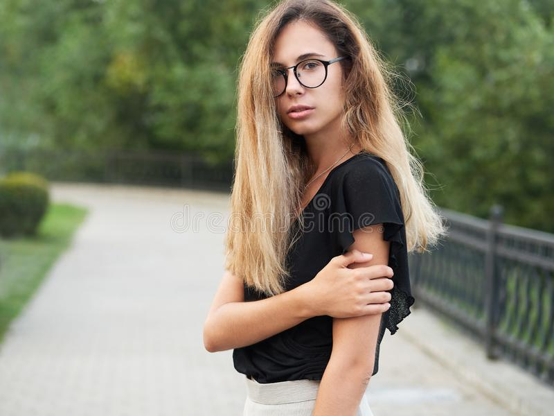 Portrait of young beautiful long hair woman wearing black blouse, holding mobile phone at summer green park path background. royalty free stock photos