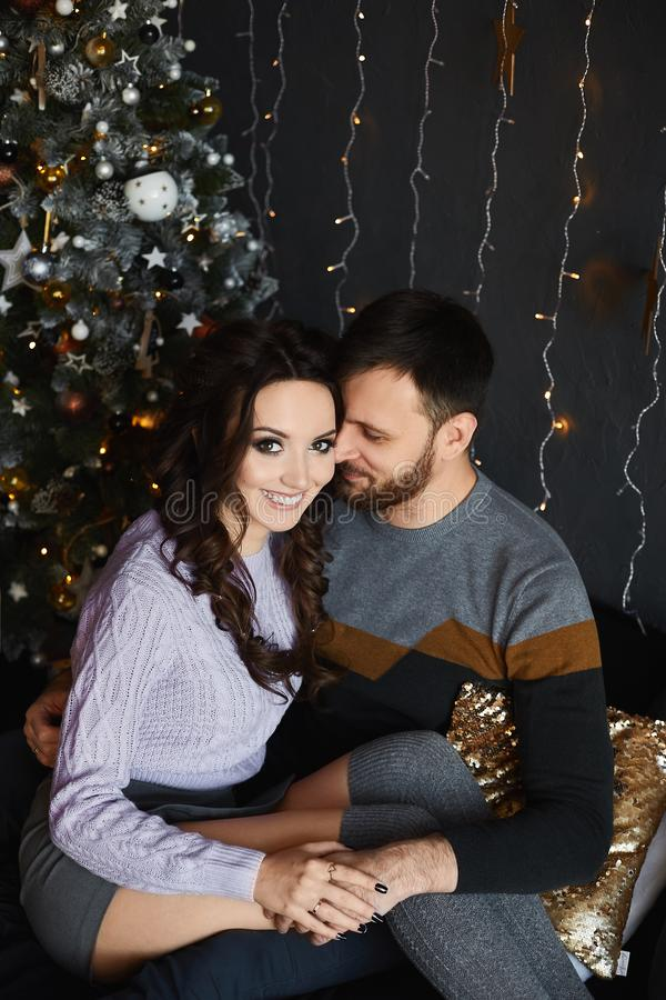 Portrait of young beautiful lovers in the Christmas interior. Handsome man and young beauty in stylish outfit spending royalty free stock photo
