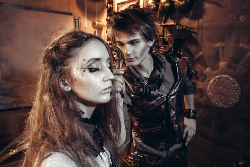 Portrait of a young beautiful loving couple in steampunk style. stock image