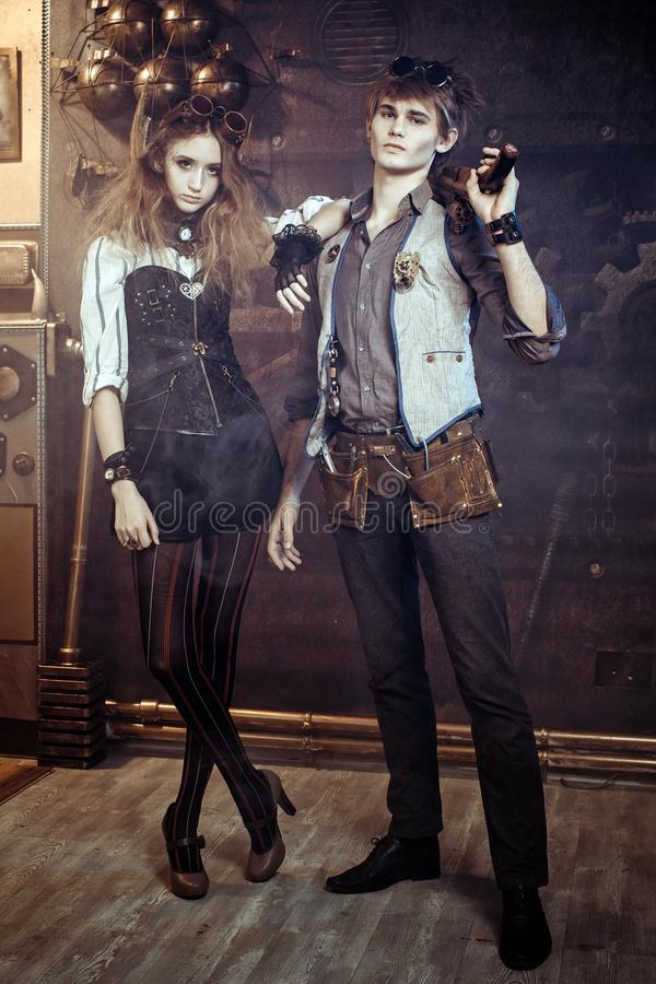 Portrait of a young beautiful loving couple in steampunk style w stock photography