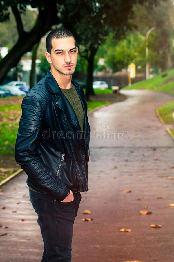 Portrait of young beautiful man outdoors, path in the park royalty free stock image