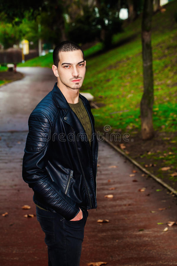 Portrait of young beautiful man outdoors, path in the park stock photos