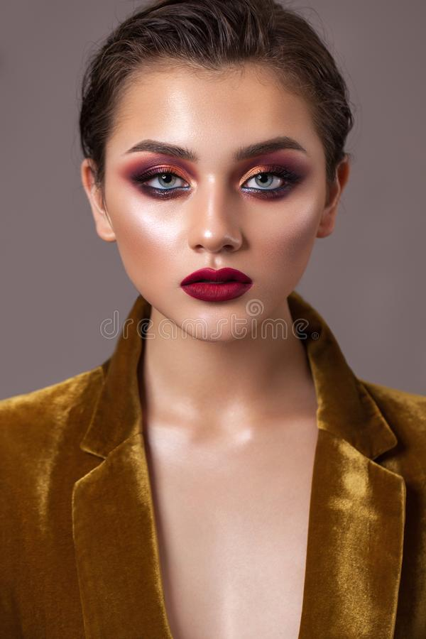 Portrait of a young beautiful model with evening make-up, red smoky eyes and lips and hair pulled back in a ponytail. Portrait of a young beautiful model with stock photography