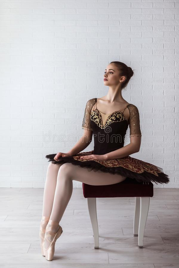 Portrait of young beautiful perfect ballerina sitting on chair indoors stock photos
