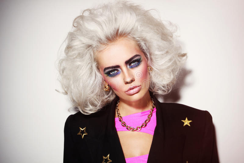 Portrait of young beautiful platinum blond woman with bold eyebrows and 80s style makeup stock photography