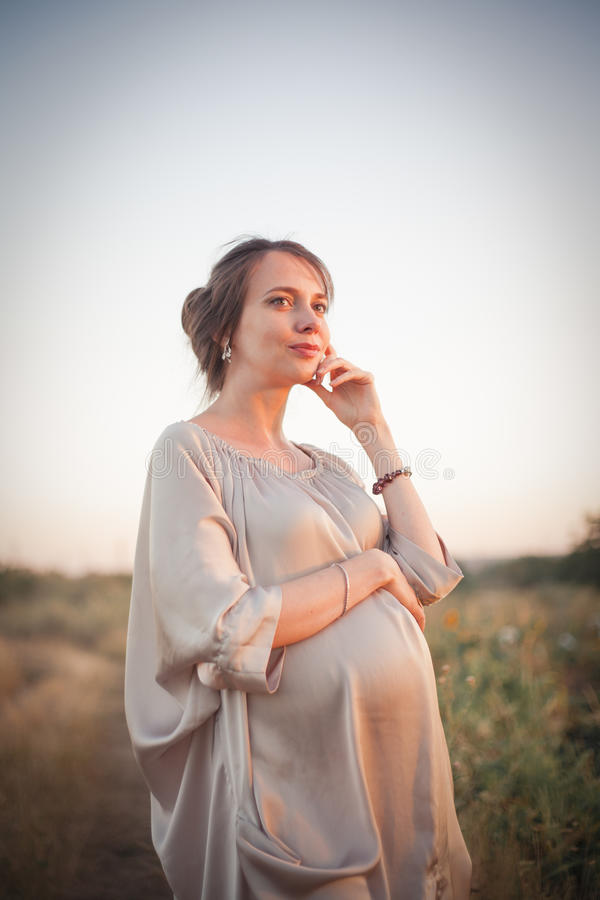 Portrait of a young beautiful pregnant woman on nature. stock images
