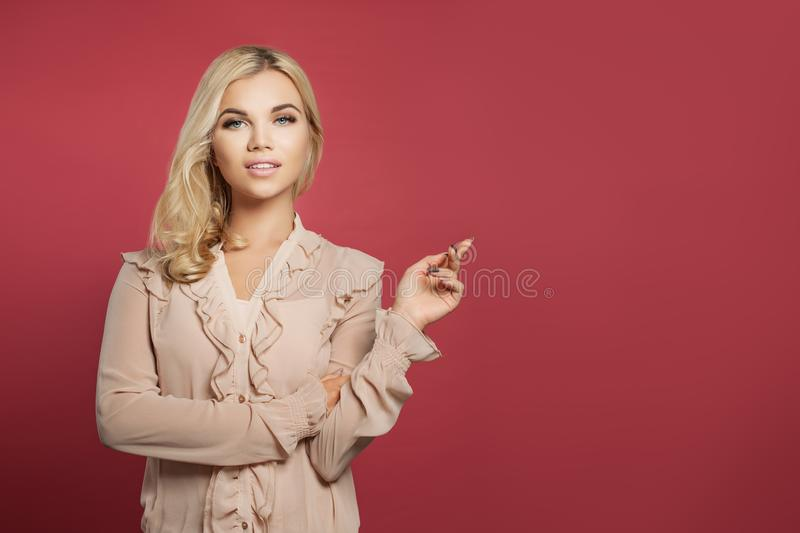 Portrait of young beautiful pretty woman pointing up on pink background. Girl pointing finger, positive emotions royalty free stock photography