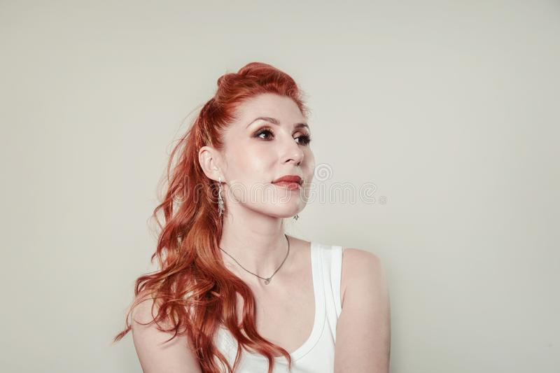 Portrait of a young beautiful red-haired woman  in gentle colors stock photo
