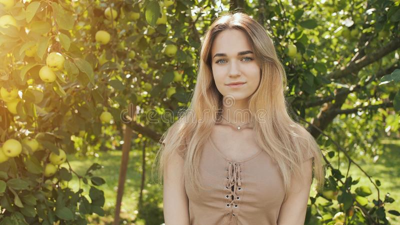 Portrait of a young beautiful seventeen-year-old blonde girl in the apple orchard. stock photography