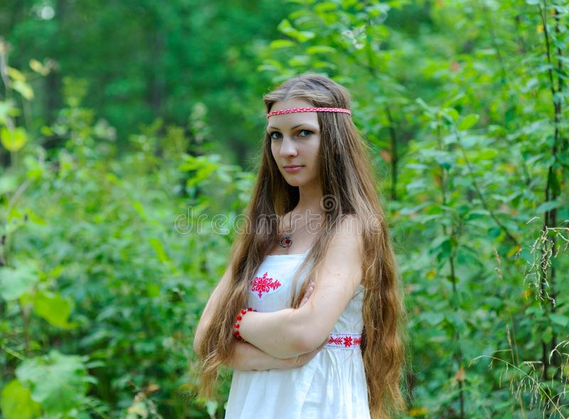 Portrait of a young beautiful Slavic girl with long hair and a Slavic ethnic dress on a background of green grass royalty free stock photo